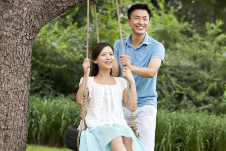 Merry young couple playing on a swing