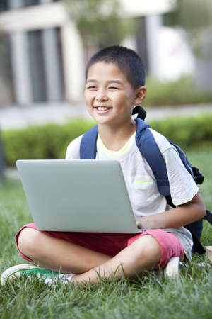 Smiling schoolboy sitting on the lawn with laptop