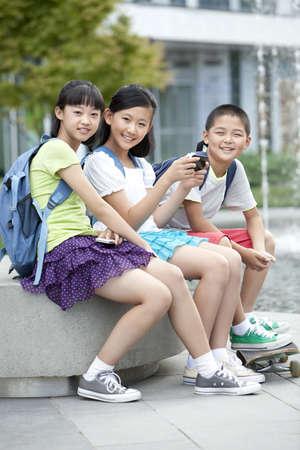 Portrait of schoolchildren playing smart phones together