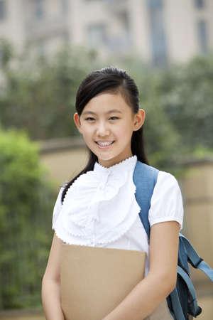 Lovely schoolgirl  in uniform with book in hand at school yard