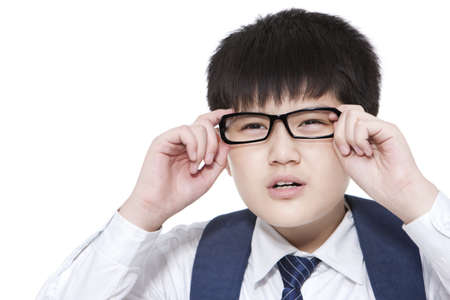 Nearsighted schoolboy having trouble seeing things clearly adjusting his glasses