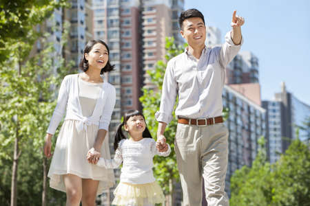Young parents with daughter strolling hand in hand