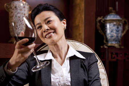 one mature woman only: Mature businesswoman enjoying wine in a luxurious room LANG_EVOIMAGES