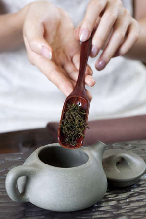people: Female hand putting tea leaves into teapot