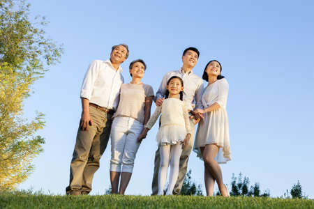 Cheerful young family looking at view in a park