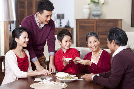 family: Cheerful family making Chinese dumplings during Chinese New Year LANG_EVOIMAGES