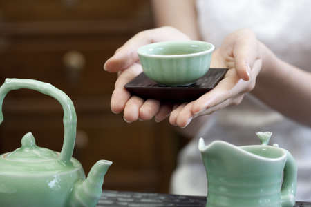 Young woman serving Chinese tea LANG_EVOIMAGES