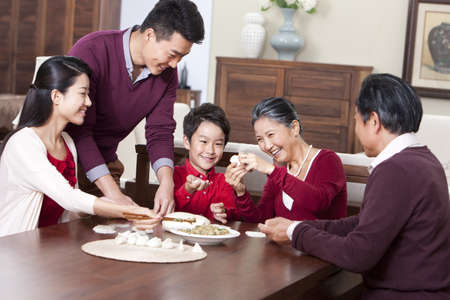 Cheerful family making Chinese dumplings during Chinese New Year LANG_EVOIMAGES