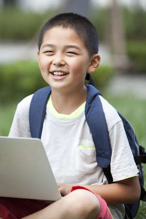 Happy schoolboy using high-tech laptop LANG_EVOIMAGES