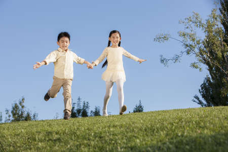 level playing field: Cute little girl and boy to be flying in a park LANG_EVOIMAGES