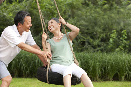 Cheerful senior couple playing on a swing