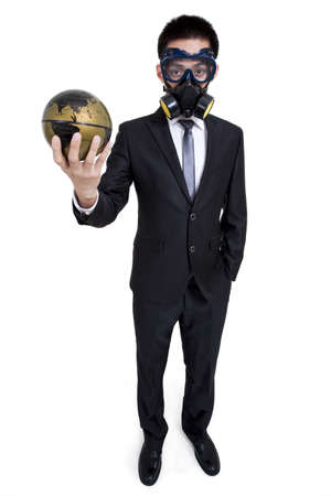 Young businessman with gas mask holding a globe