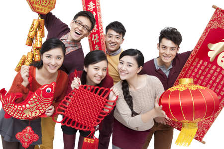 Cheerful young friends with decorations in Chinese New Year
