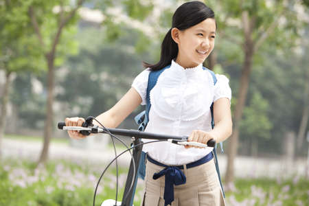 Happy schoolgirl in uniform with bicycle outdoors LANG_EVOIMAGES