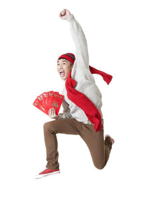 envelops: Excited young man celebrating Chinese New Year with red envelops