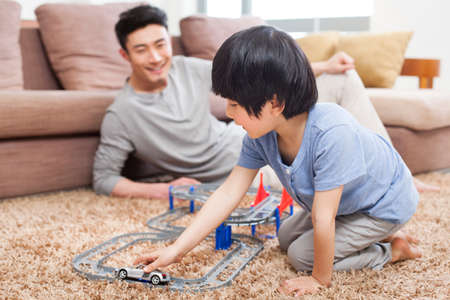 oriental rug: Father and son playing toy car in living room
