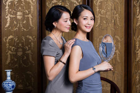 screen partition: Elegant mother and daughter with mirror in hand LANG_EVOIMAGES