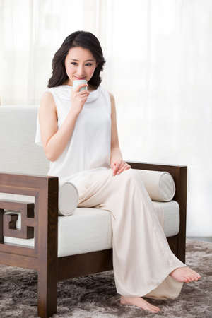 oriental rug: Happy young woman drinking tea LANG_EVOIMAGES