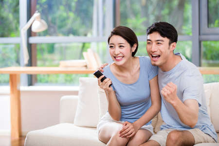 open windows: Excited young couple watching TV