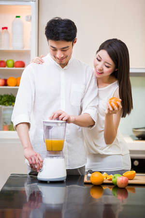 turn away: Young couple using juicer in kitchen