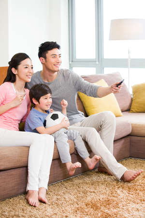 oriental rug: Excited family watching football on TV