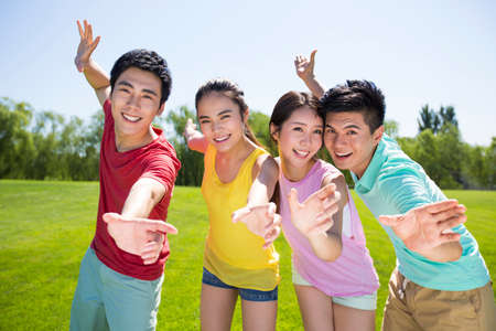 Group photo of four cheerful young adults standing on grass