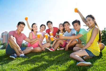 Cheerful young adults holding juice sitting on grass
