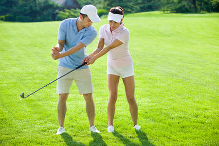 Young man teaching his girlfriend how to play golf