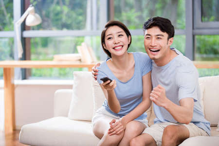 changing channels: Young couple changing channels