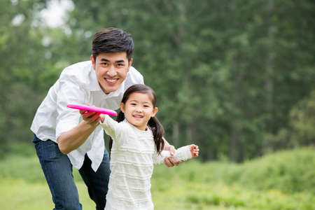 Father and daughter playing frisbee