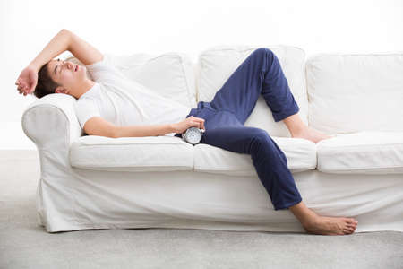 Young man sleeping on couch LANG_EVOIMAGES