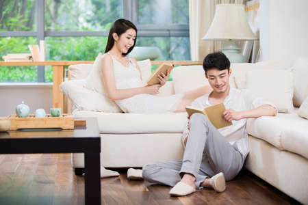 Cheerful young couple reading book in living room