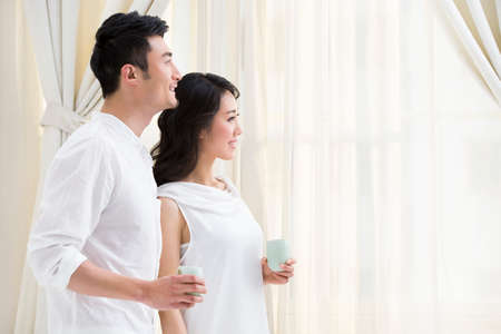hot asian: Happy young couple looking out of window