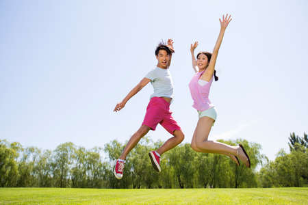 Cheerful young man and young woman jumping on grass