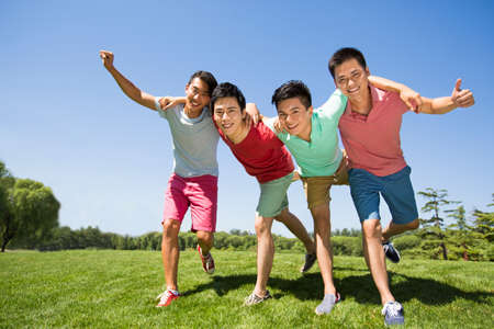 Four cheerful young men standing arm in arm on grass