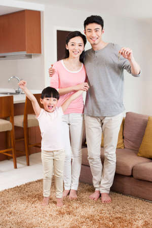 oriental rug: Portrait of happy family cheering with key in hand LANG_EVOIMAGES