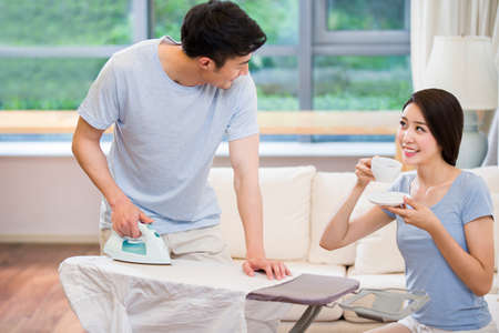 Young man ironing and wife drinking LANG_EVOIMAGES
