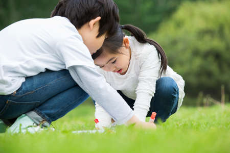 Boy and girl drawing on the grass
