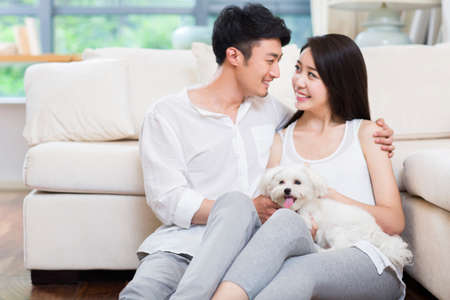 Cheerful young couple and a cute dog