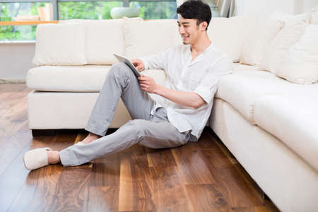 Cheerful young man using digital tablet in living room