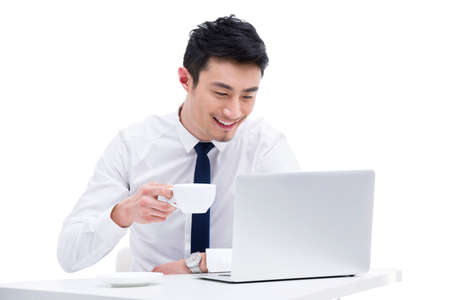 Businessman using laptop whilst drinking coffee from cup