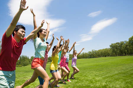 Cheerful young adults raising arms running on grass