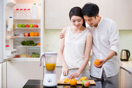 Young woman cutting oranges with husband in kitchen LANG_EVOIMAGES