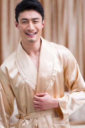 oriental bathrobe: Cheerful young man in bedroom