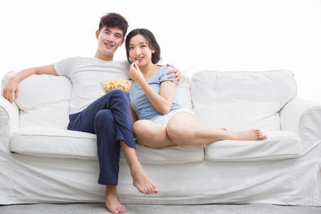 Young couple watching movie in living room