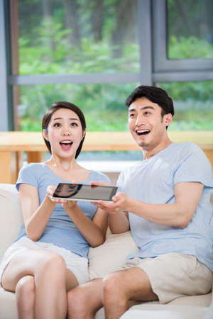 open windows: Young couple cheering with digital tablet