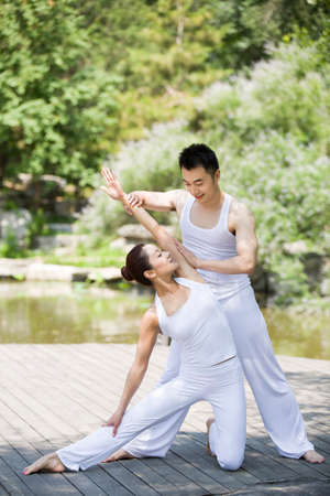 Yoga instructor helping woman with pose