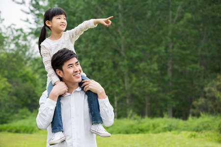 Happy father carrying daughter on shoulders LANG_EVOIMAGES