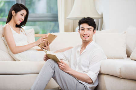 floor lamp: Cheerful young couple reading book in living room