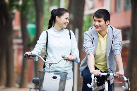Young couple  riding bicycle on campus LANG_EVOIMAGES